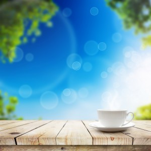 Cup with hot drink on table over Green bokeh and sunlight. Beauty morning breakfast spring background
