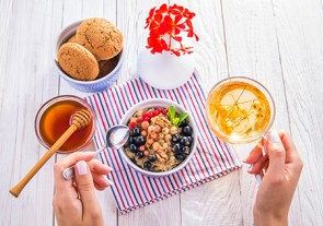 Oatmeal porridge with berries, tea and cookies for breakfast on wooden table
