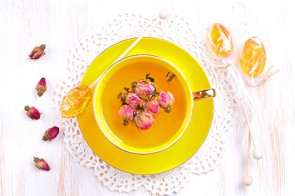 A cup of green tea with roses and a spoon of honey