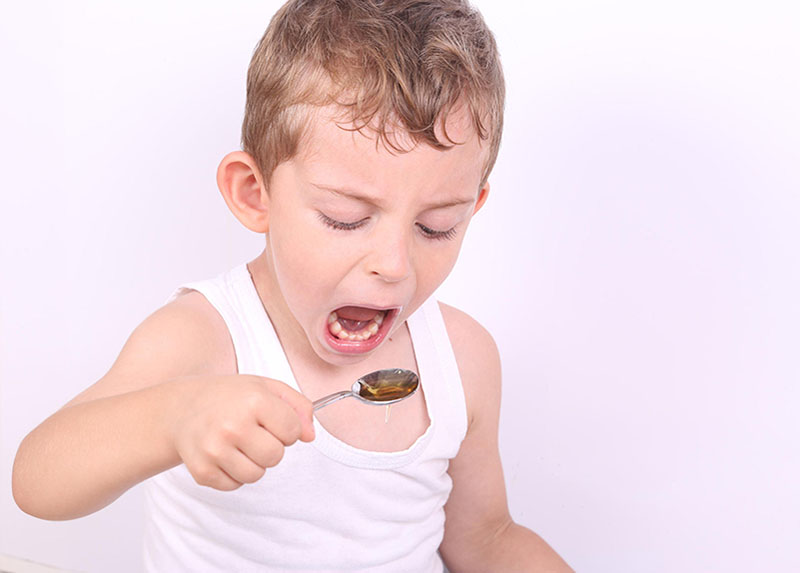 a boy holding a spoon of honey